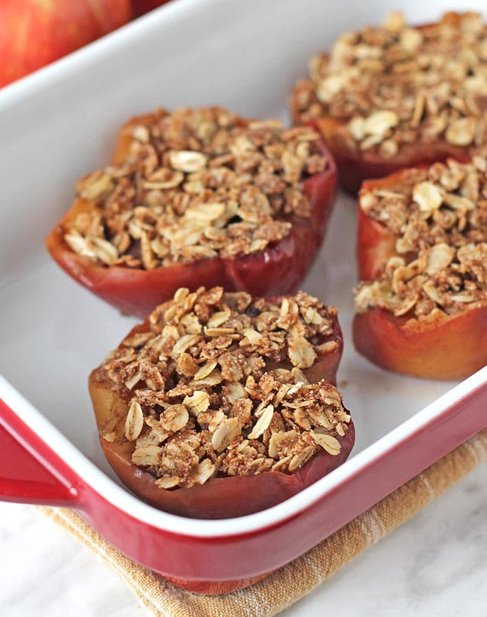 Four baked apple halves in a red and white baking dish.