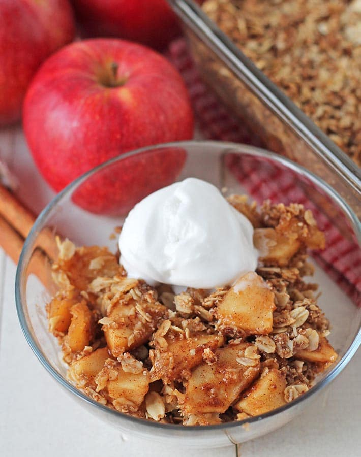 Vegan apple crisp in a bowl, bowl is sitting on a white table.