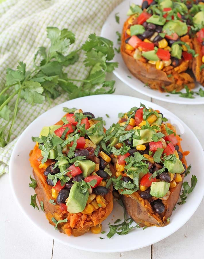 Loaded baked sweet potatoes on a white plate.