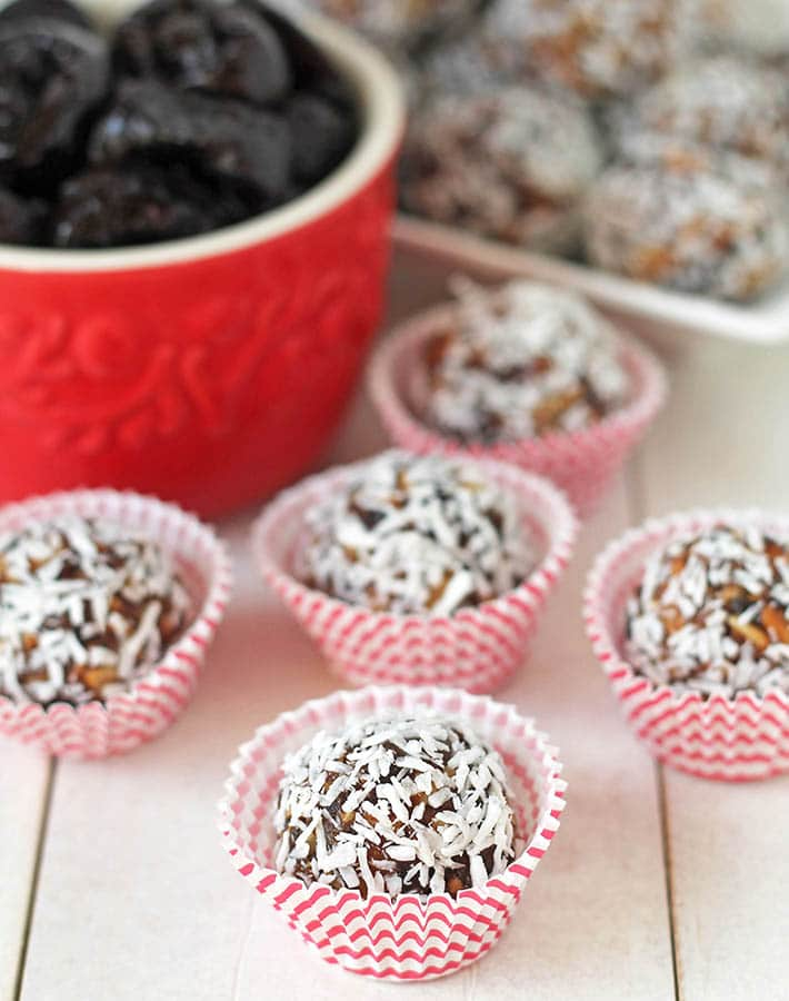 Prune power balls in individual mini muffin cups on a white table.