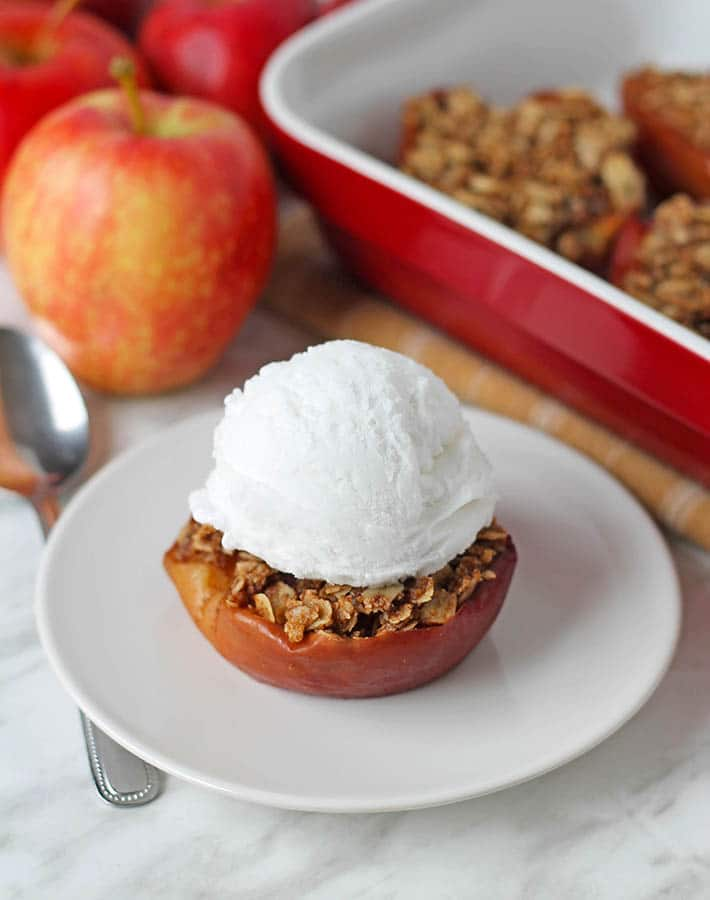 Oven baked apple half on a plate with ice cream on top.