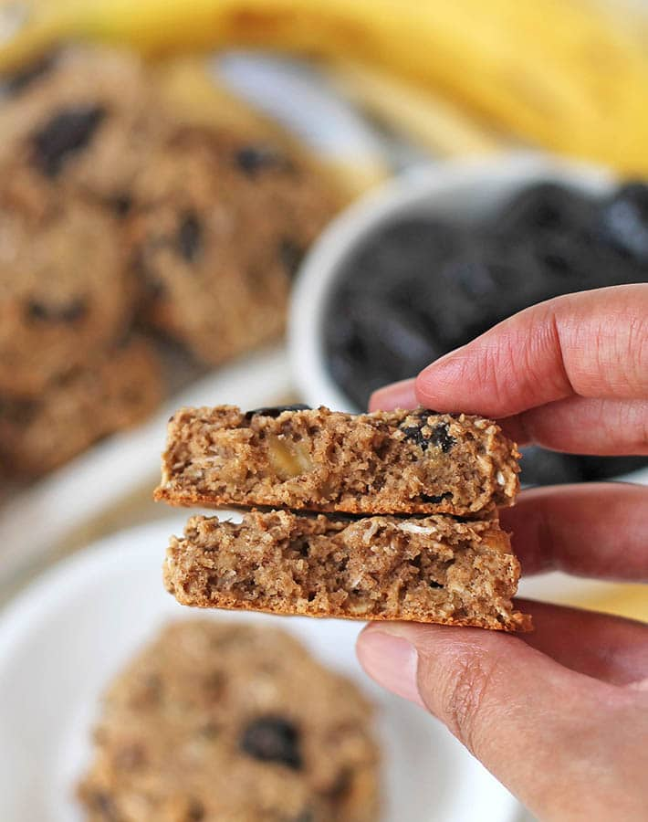 A hand holding an oatmeal breakfast cookie that has been split in two to show the inner texture.