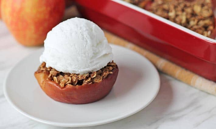 Close up shot of a gluten free baked apple with a scoop of ice cream on top.