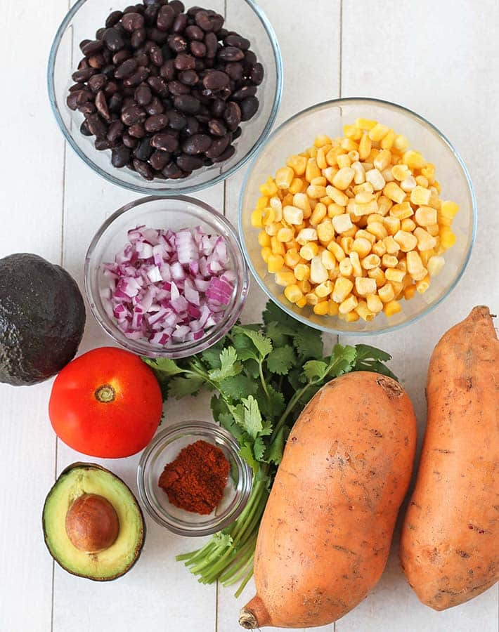 Ingredients for Mexican stuffed sweet potatoes on a white wood table.