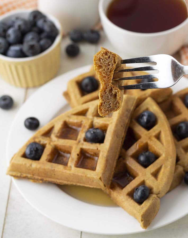 A fork holding up a piece of a gluten free sweet potato waffle to show the inner fluffy texture.