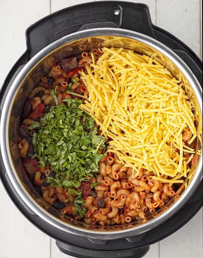 An Instant Pot filled with chili mac, cilantro and vegan cheese sits on top to be mixed in.