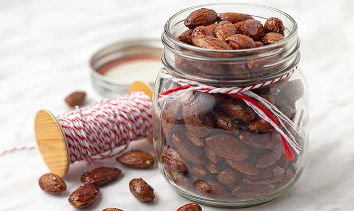 A jar of maple roasted almonds in a small mason jar.