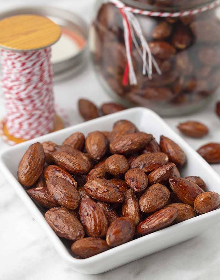 Cinnamon spiced almonds in a small dish, a jar of more almonds sits behind.
