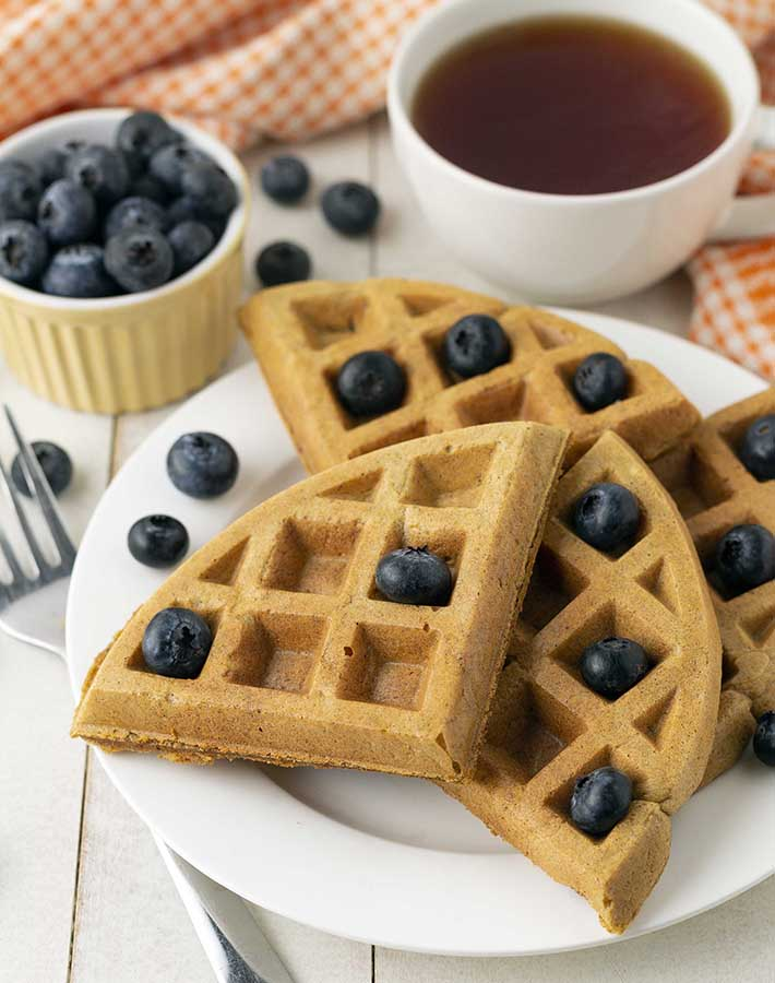 A plate of sweet potato waffles on a white plate, waffles are garnished with fresh blueberries.