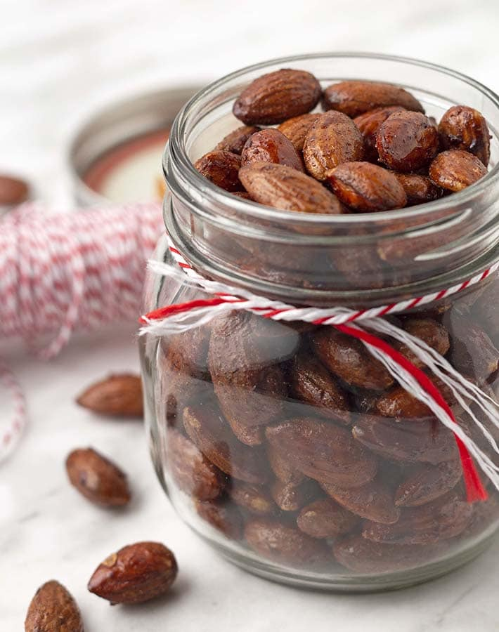 An open mason jar filled with maple glazed almonds.