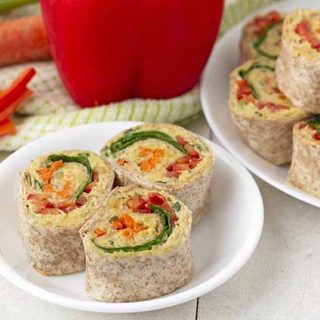 Three vegetable pinwheels on a small white plate.