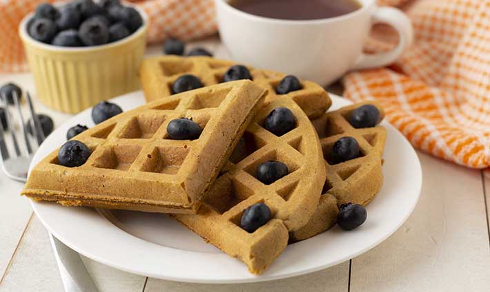 Close up shot of a plate of gf sweet potato waffles that are garnished with fresh blueberries..
