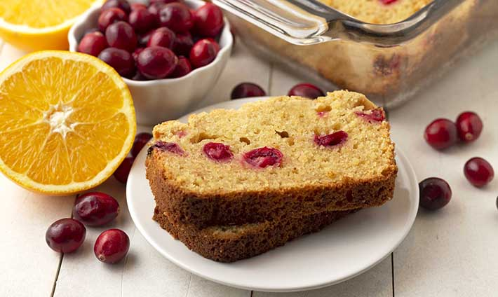 Two slices of gluten free cranberry orange bread on a plate, fresh canberries and oranges are around the plate.
