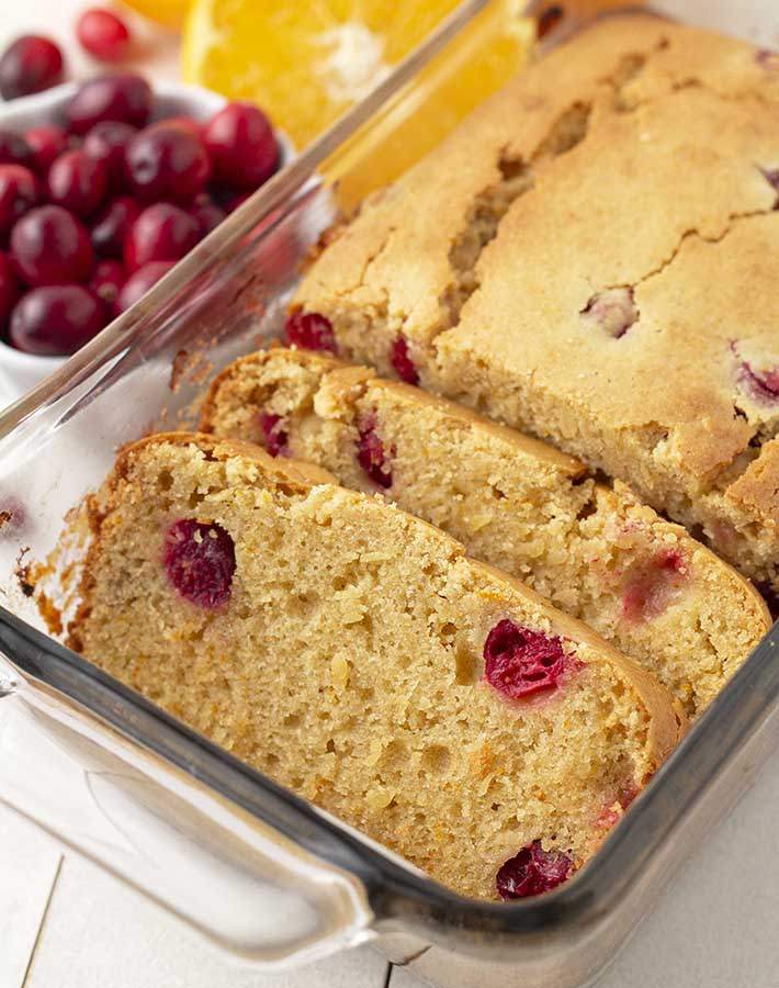 Slices of gluten free cranberry orange loaf in a glass baking dish.