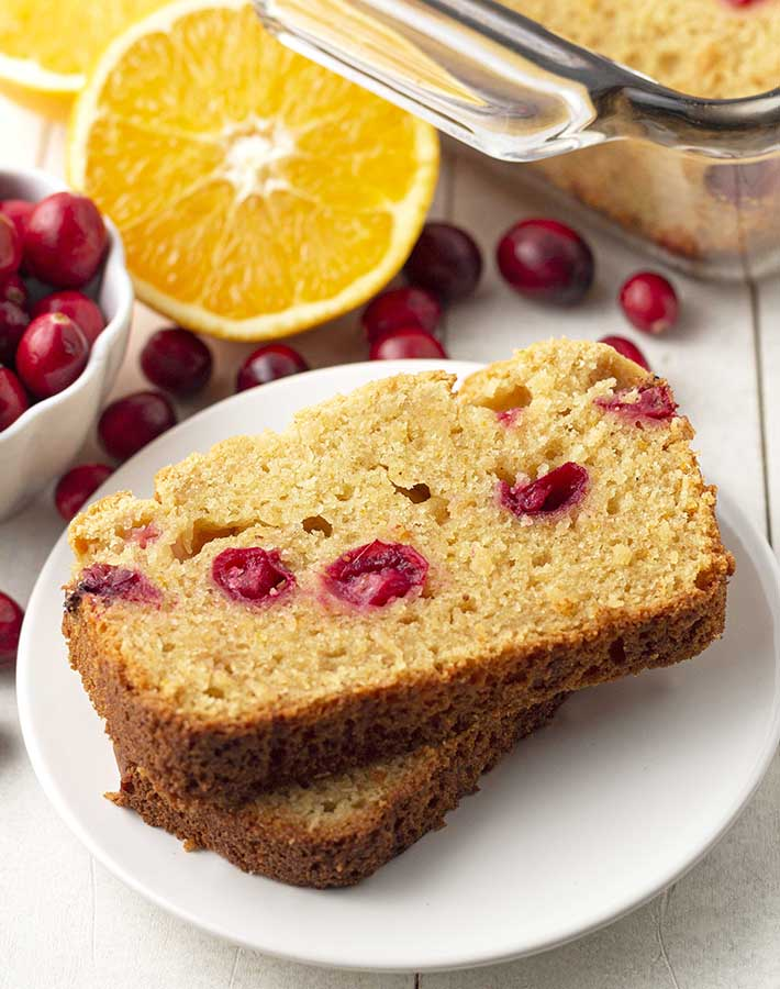 Two slices of cranberry orange bread on a white plate.