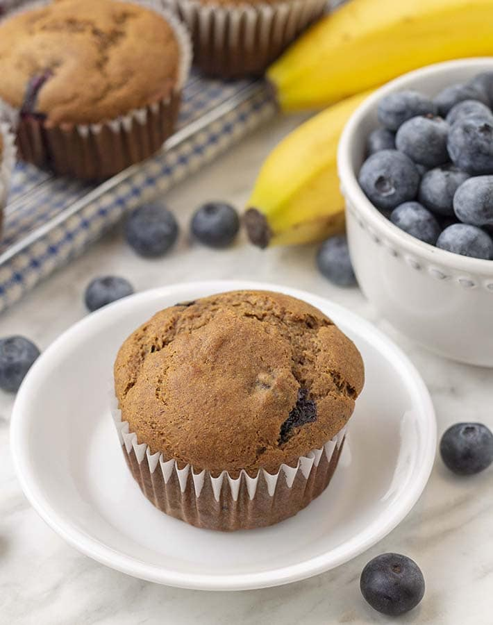 A vegan banana blueberry muffin sitting on a small white plate, more muffins sit behind the plate and fresh blueberries and bananas are on the table.