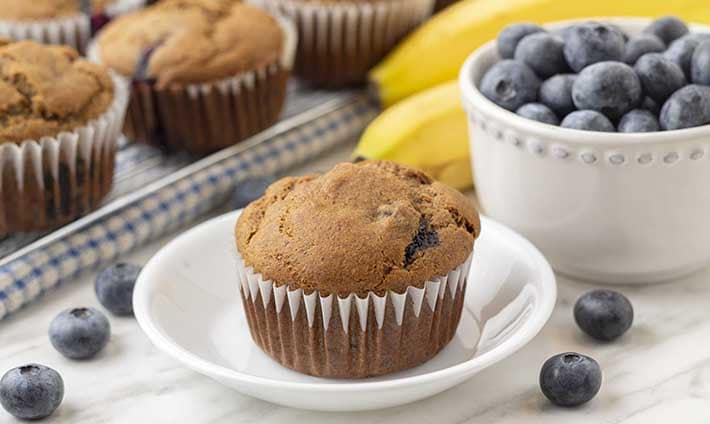 A vegan banana blueberry muffin on a plate with fresh blueberries on the table around the plate.