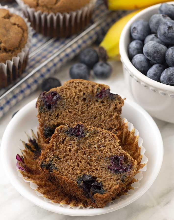 A banana blueberry gluten free muffin split in half on a small plate.