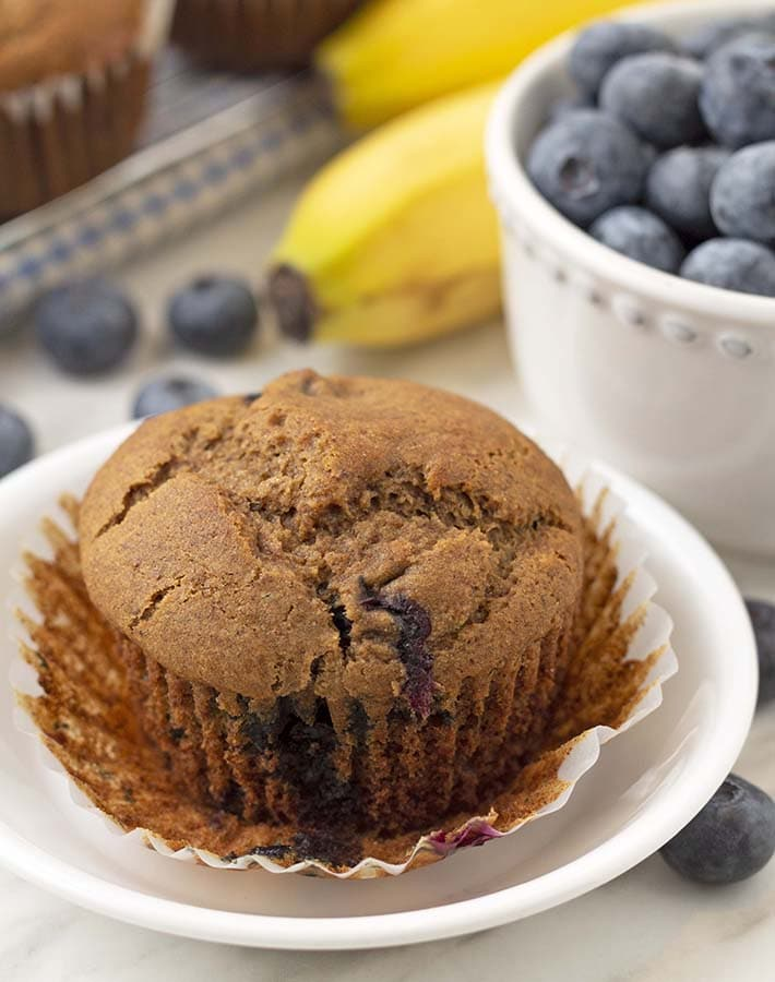 Close up shot of a gluten free banana and blueberry muffin on a plate with the muffin wrapper peeled off.