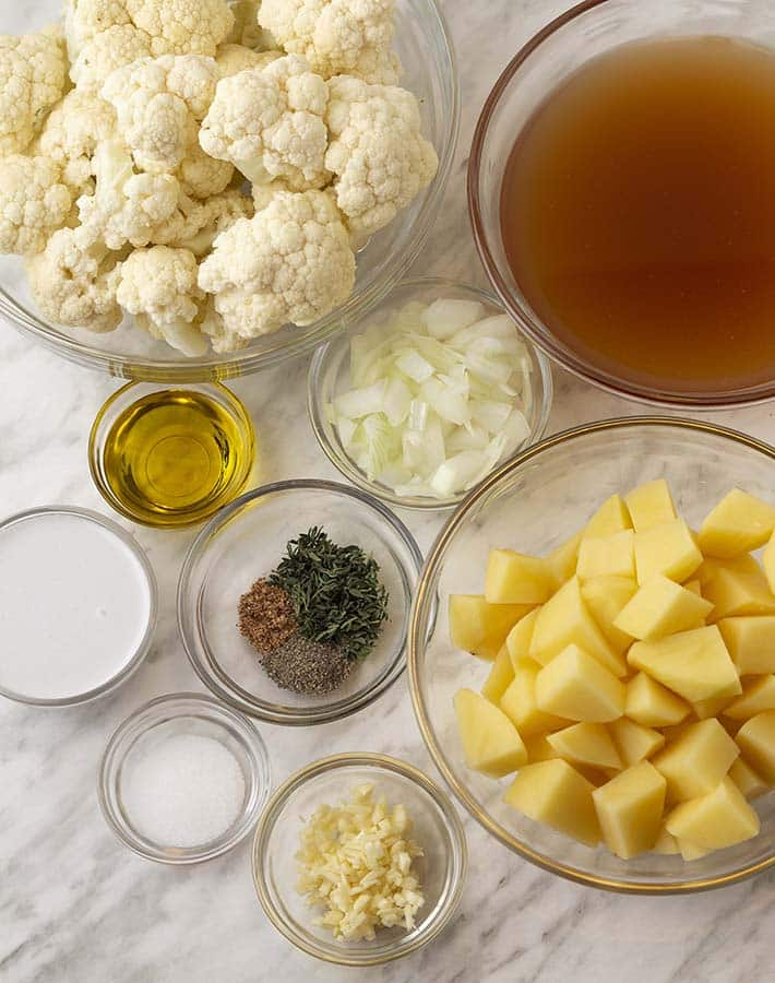 Overhead shot of the ingredients needed to make vegan cauliflower and potato soup, all ingredients are in separate glass bowls.