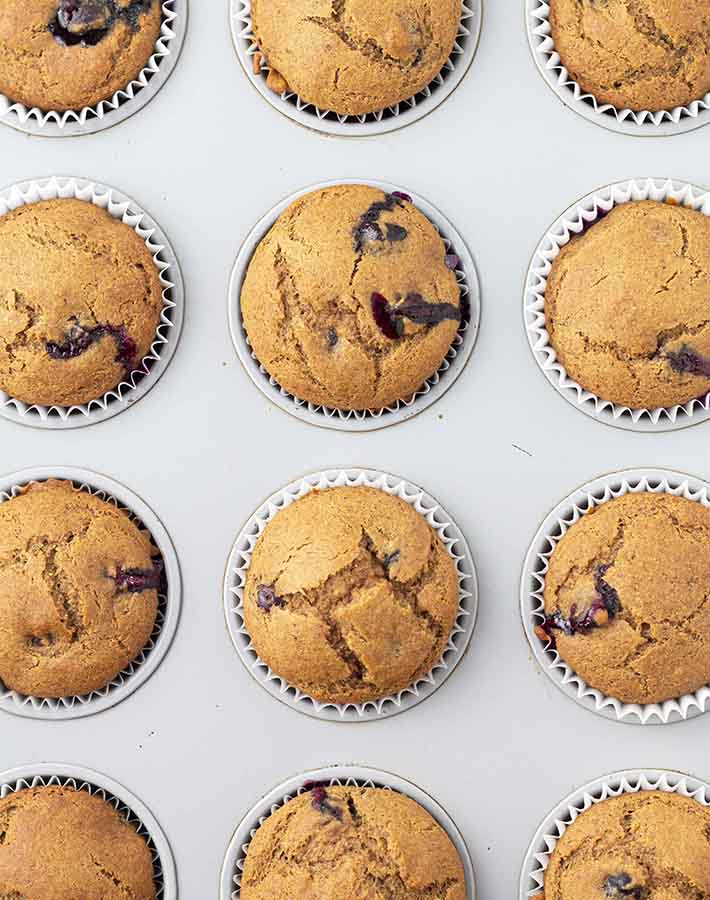 Overhead shot of gluten free blueberry banana muffins in a muffin pan fresh out of the oven.