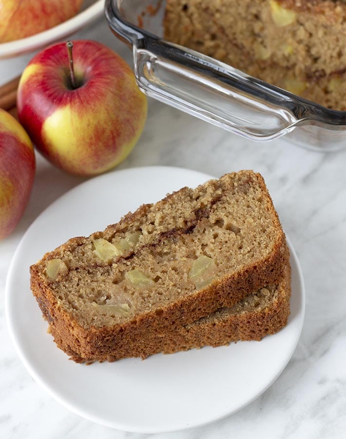 Two slices of gluten free apple cinnamon bread on a small white plate.