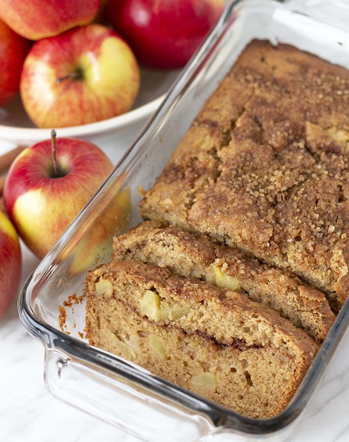 A loaf of apple bread in a glass baking dish, two pieces have been sliced and sit in front of the loaf.