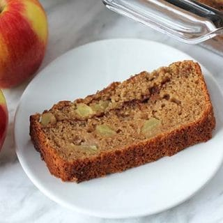 A slice of vegan applesauce bread on a small white plate.