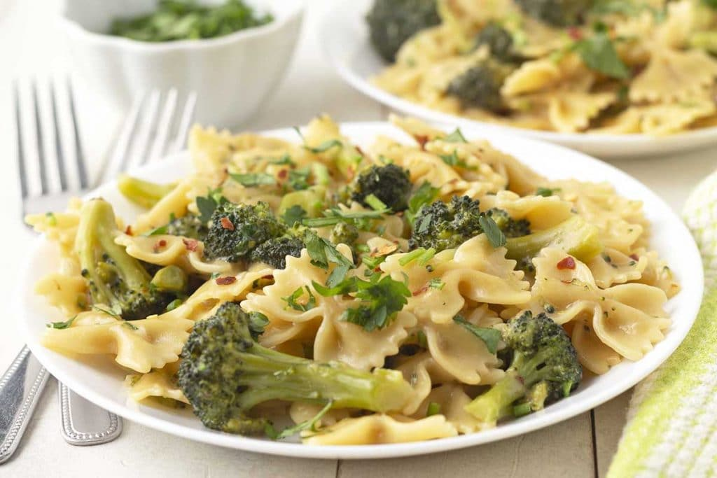 Creamy vegan broccoli pasta on a white plate, two forks sit to the left of the plate.