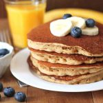 Four banana pancakes on a white plate with fresh slices of banana and blueberries on top.