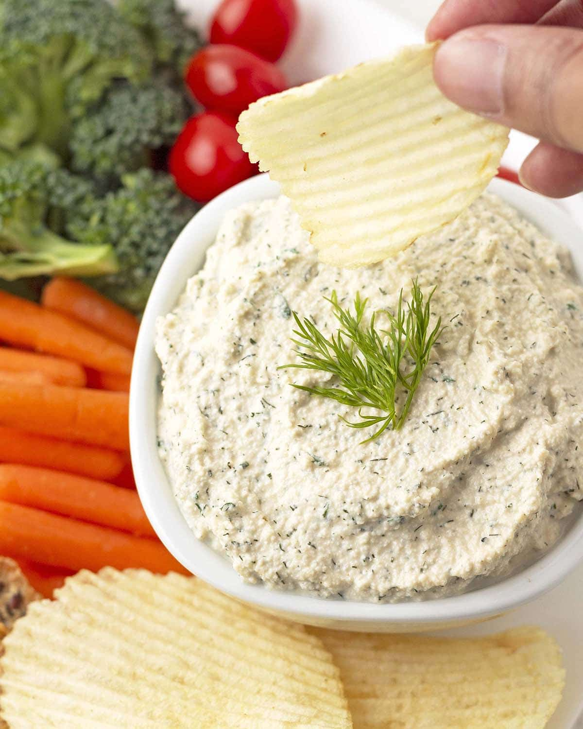 A hand dipping a potato chip into a bowl of dip, veggies and chips surround the bowl.