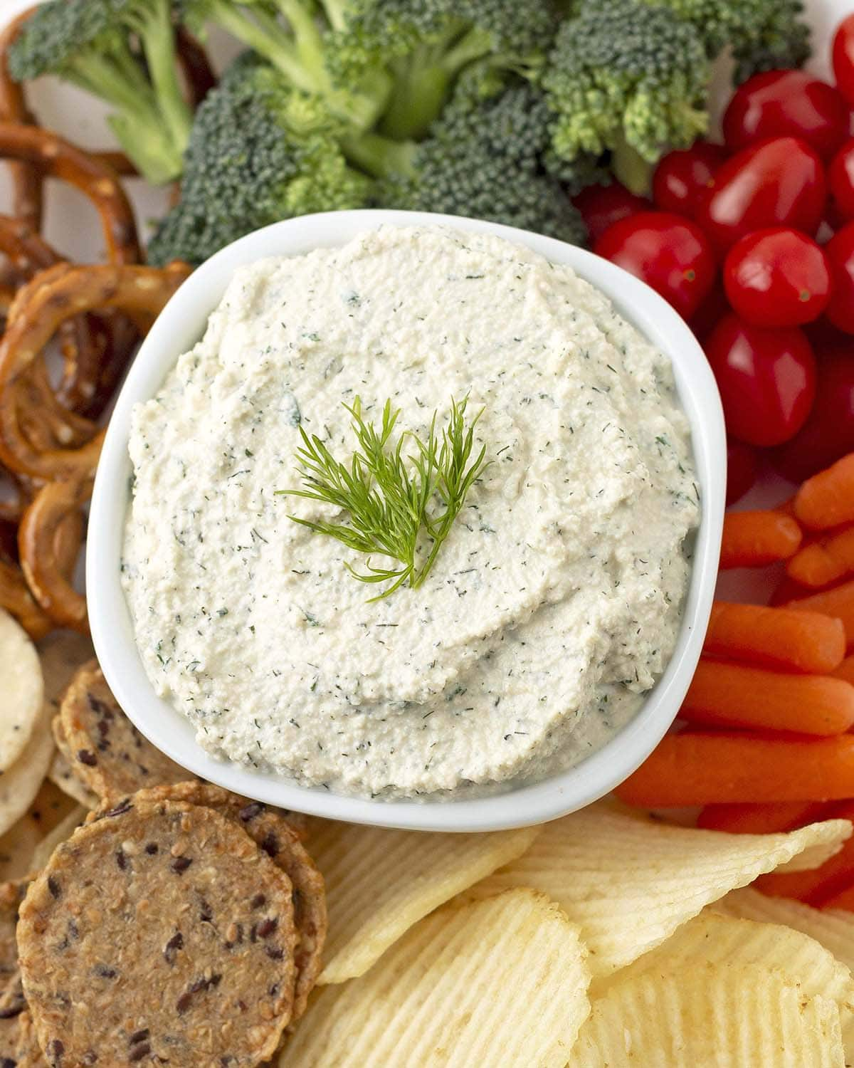 An overhead shot of a bowl of dill dip, the bowl is surrounded by fresh vegetables, chips, and crackers.