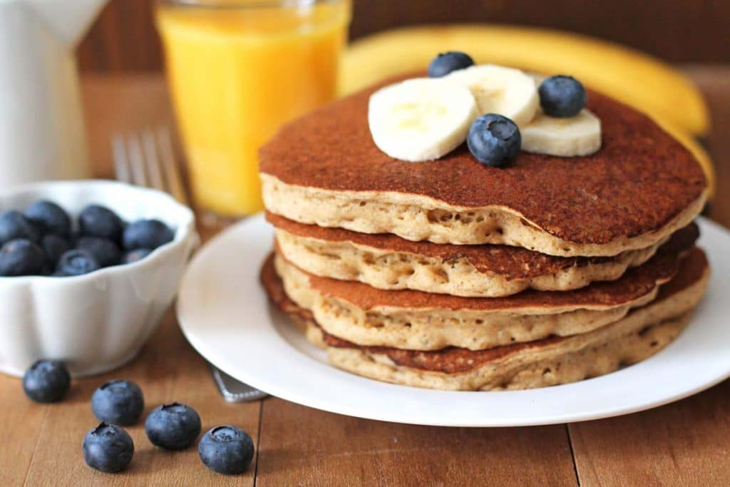 A stack of four banana pancakes sitting on a white plate, pancakes are topped with sliced bananas and fresh blueberries.