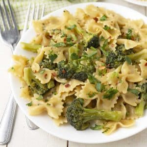 Close up shot of a plate of bow tie pasta and broccoli, two forks sit to the left of the plate.