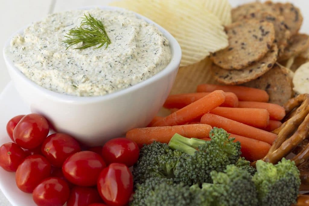 A bowl of dill dip on a plate, the plate is filled with fresh vegetables, chips, crackers, and pretzels for dipping.