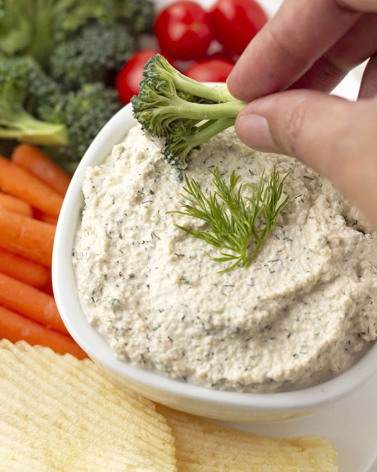 A hand dipping a piece of fresh broccoli into a bowl of dip.