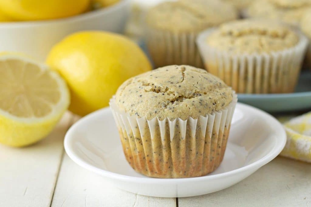 A muffin sitting on a white plate, fresh lemons sit behind the plate as well as another plate of muffins.