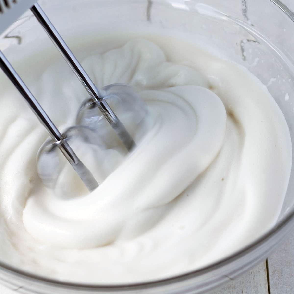 Close up image of aquafaba being whipped with a hand mixer in a glass bowl.