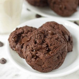 A close up shot of three double chocolate cookies on a small white plate.