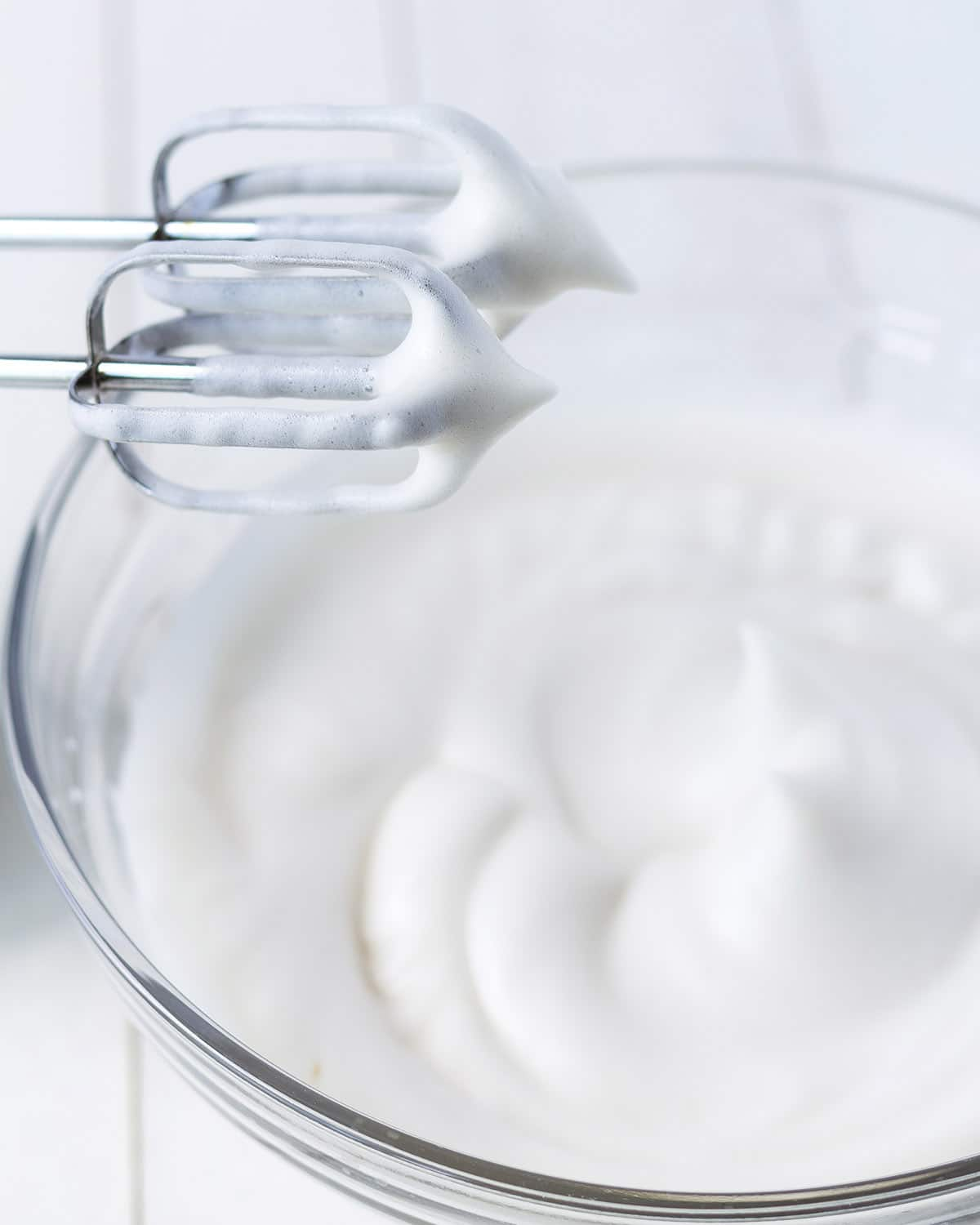 Image shows a hand mixer with a bowl of whipped aquafaba that has reached stiff peak stage.