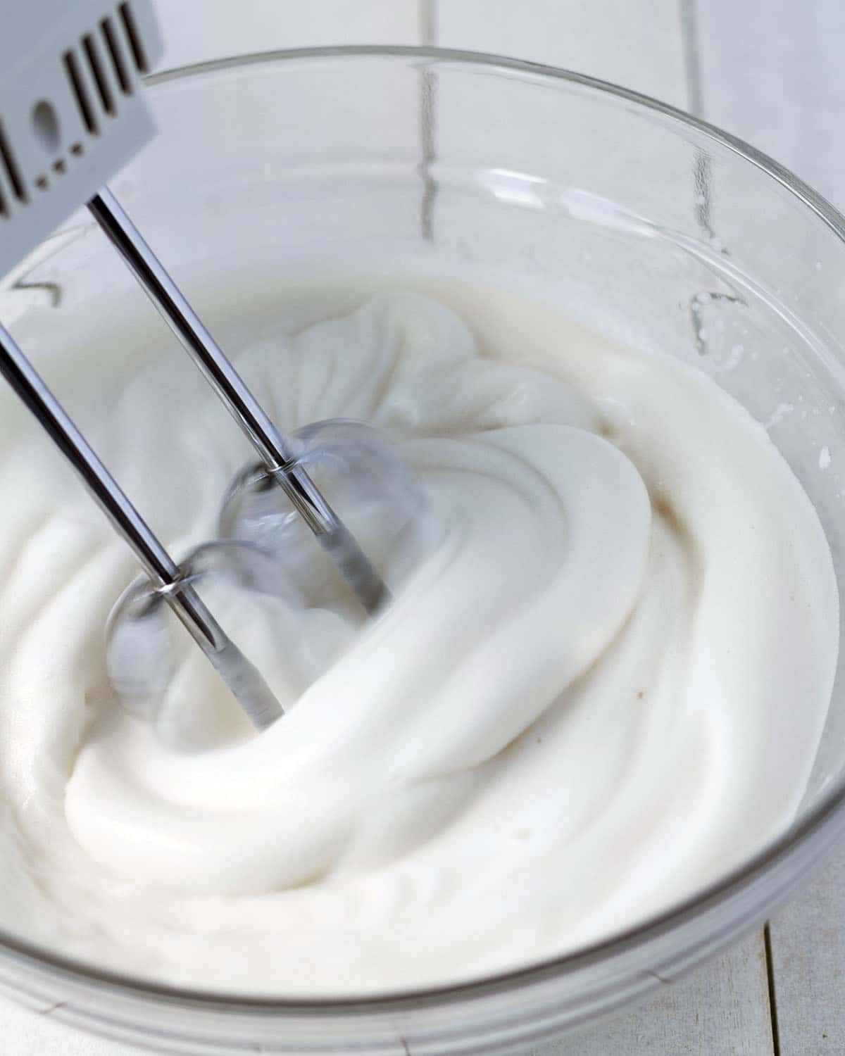 Image shows aquafaba being whipped with a hand mixer in a glass bowl.