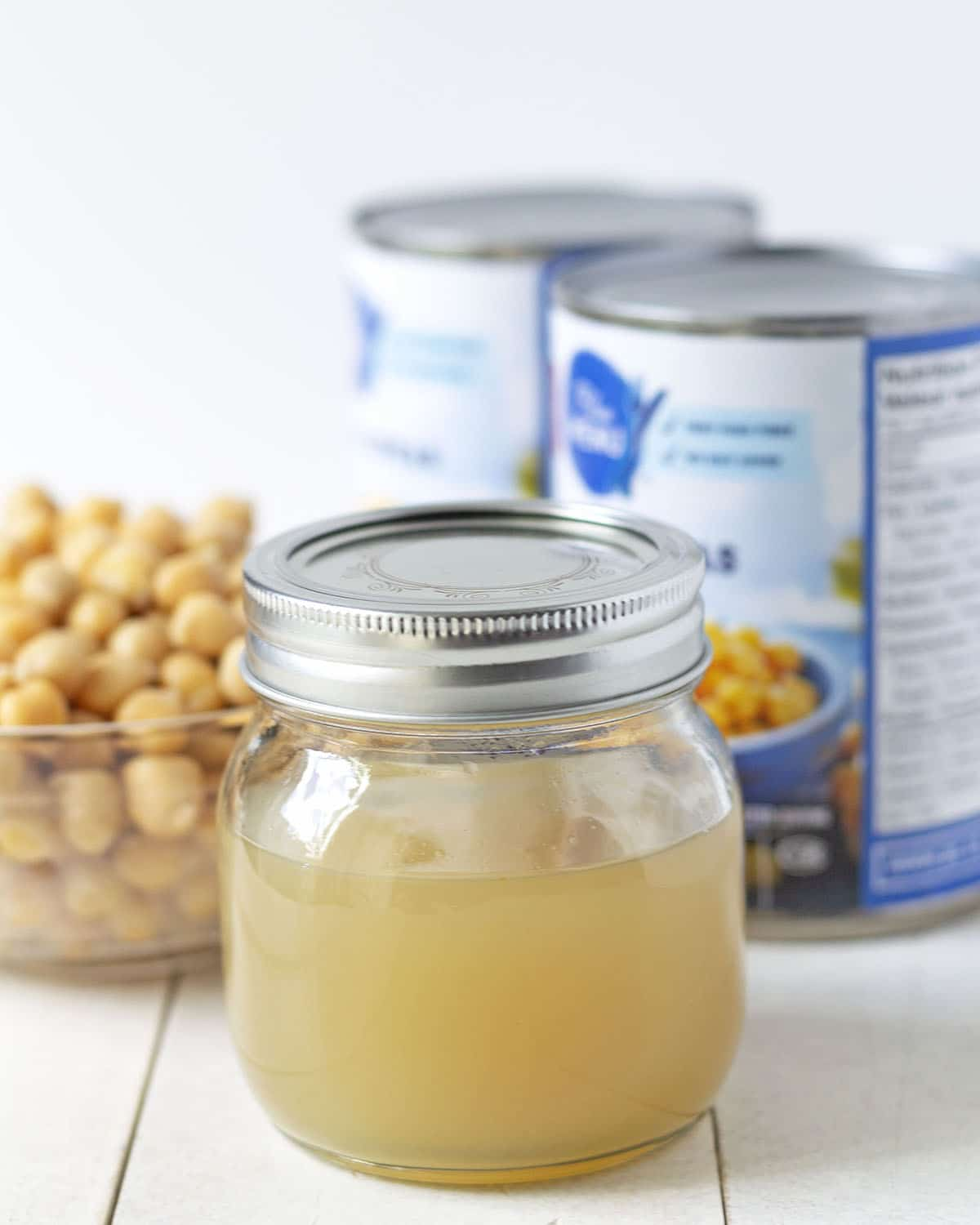 Image shows a jar of aquafaba egg replacement sitting on a white table, two cans of chickpeas and a bowl of chickpeas sit behind the jar.