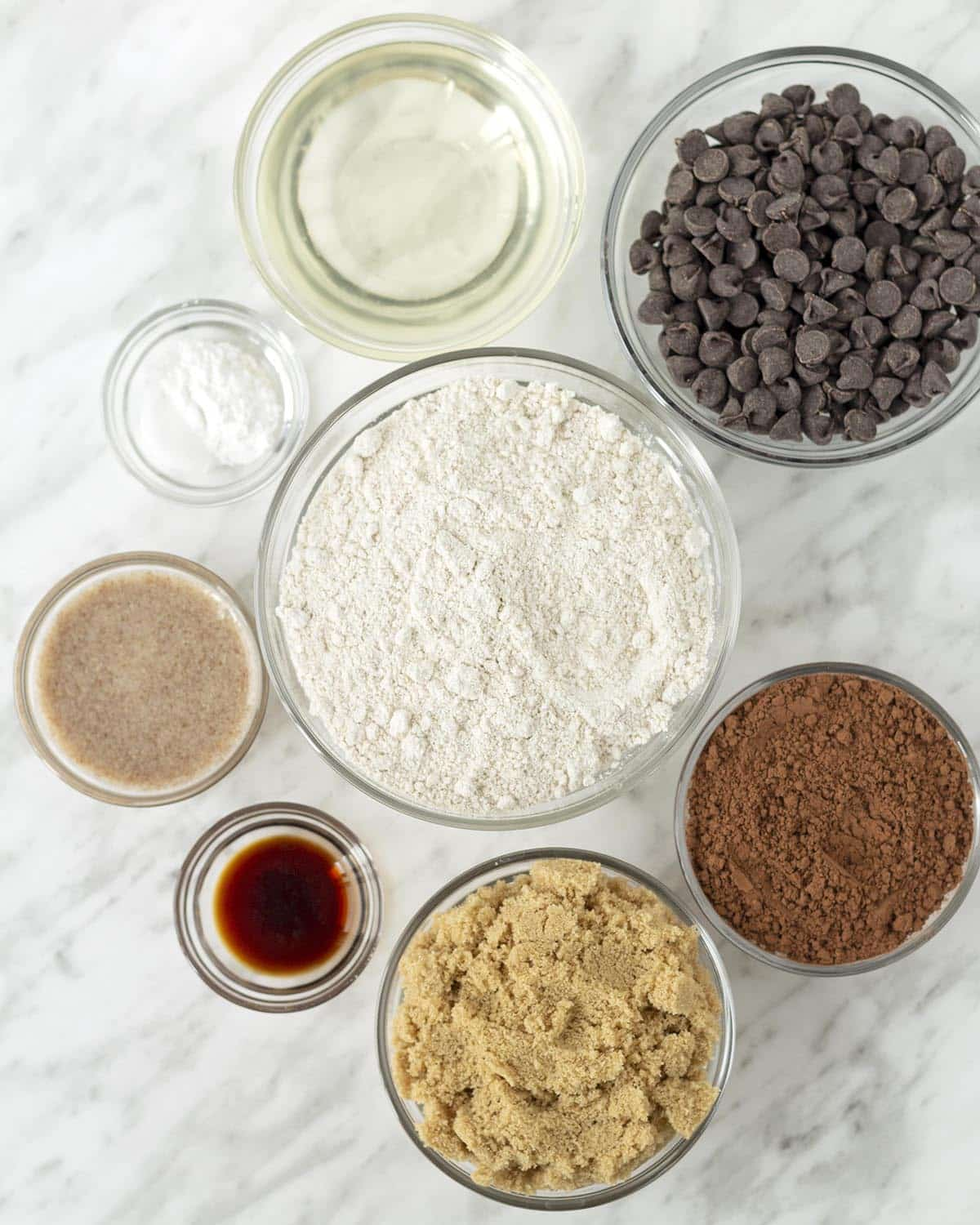 An overhead shot of the ingredients needed to make these cookies, all ingredients are in separate glass bowls.