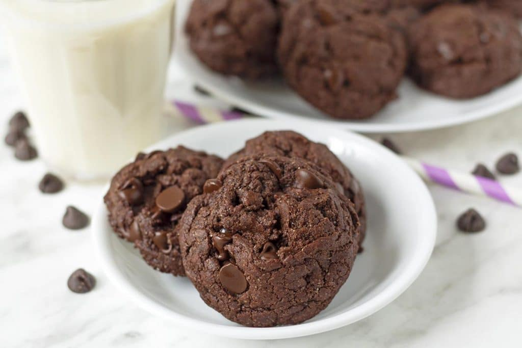 A close up shot of three double chocolate cookies sitting on a small white plate.