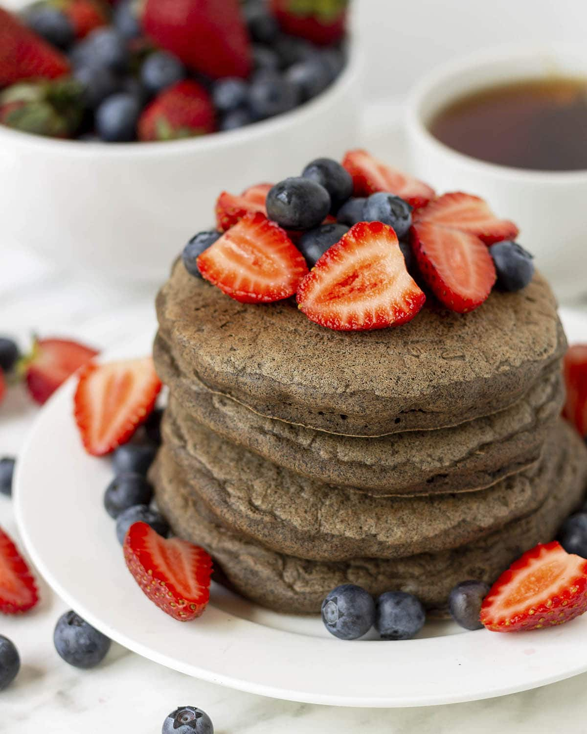 A stack of four buckwheat pancakes on a white plate, fresh blueberries and strawberries garnish the pancakes and plate.