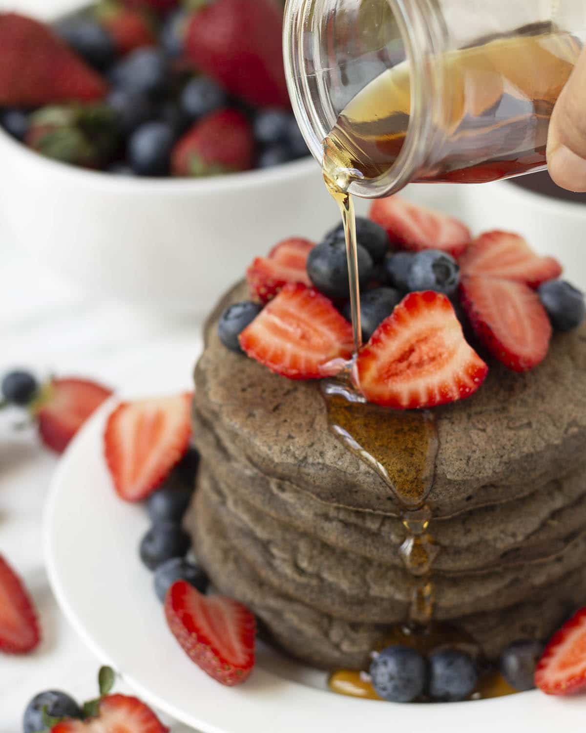 Maple syrup being poured from a small glass jar onto a stack of pancakes that are garnished with fresh berries.