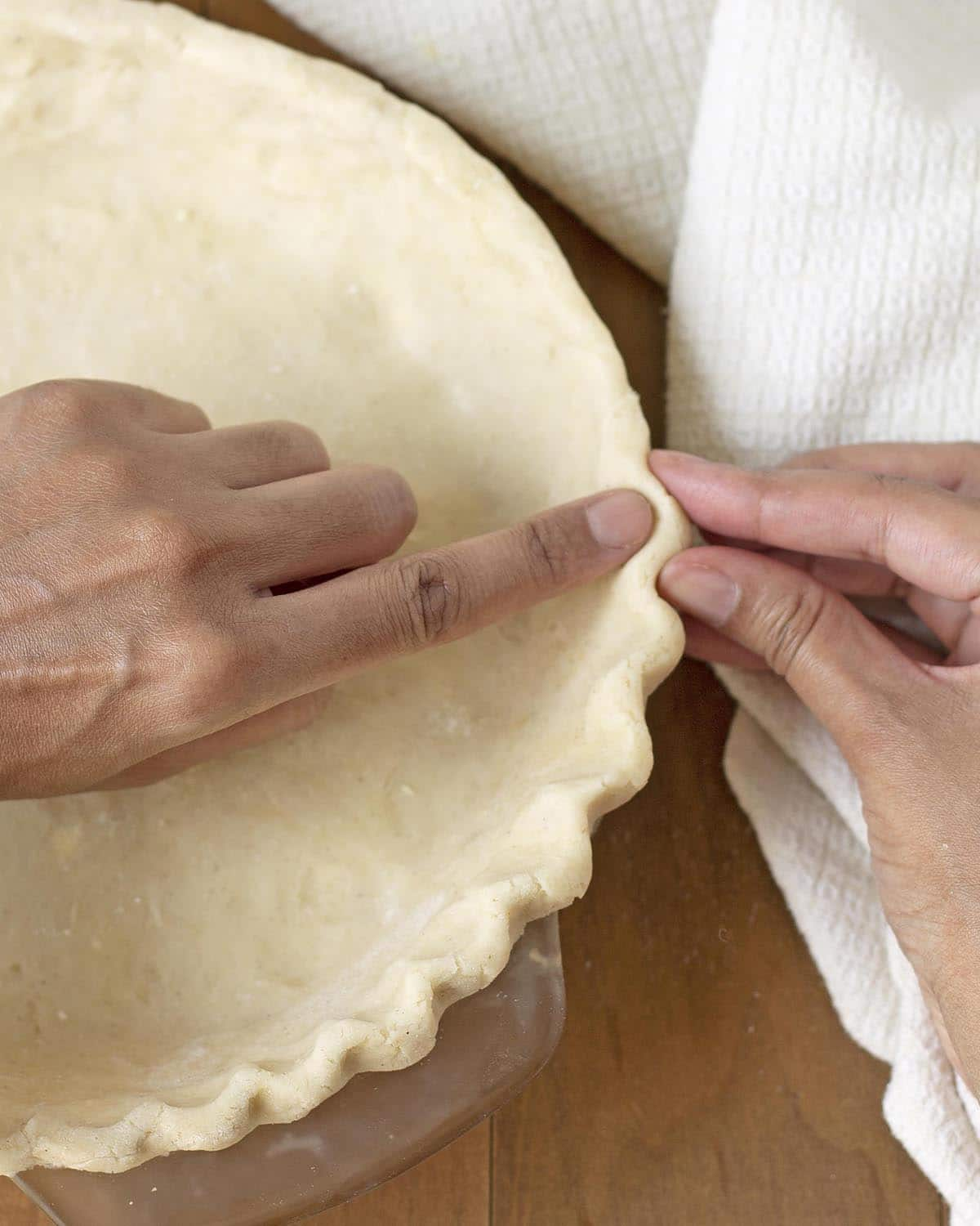 Hands crimping the edge of a pie crust.
