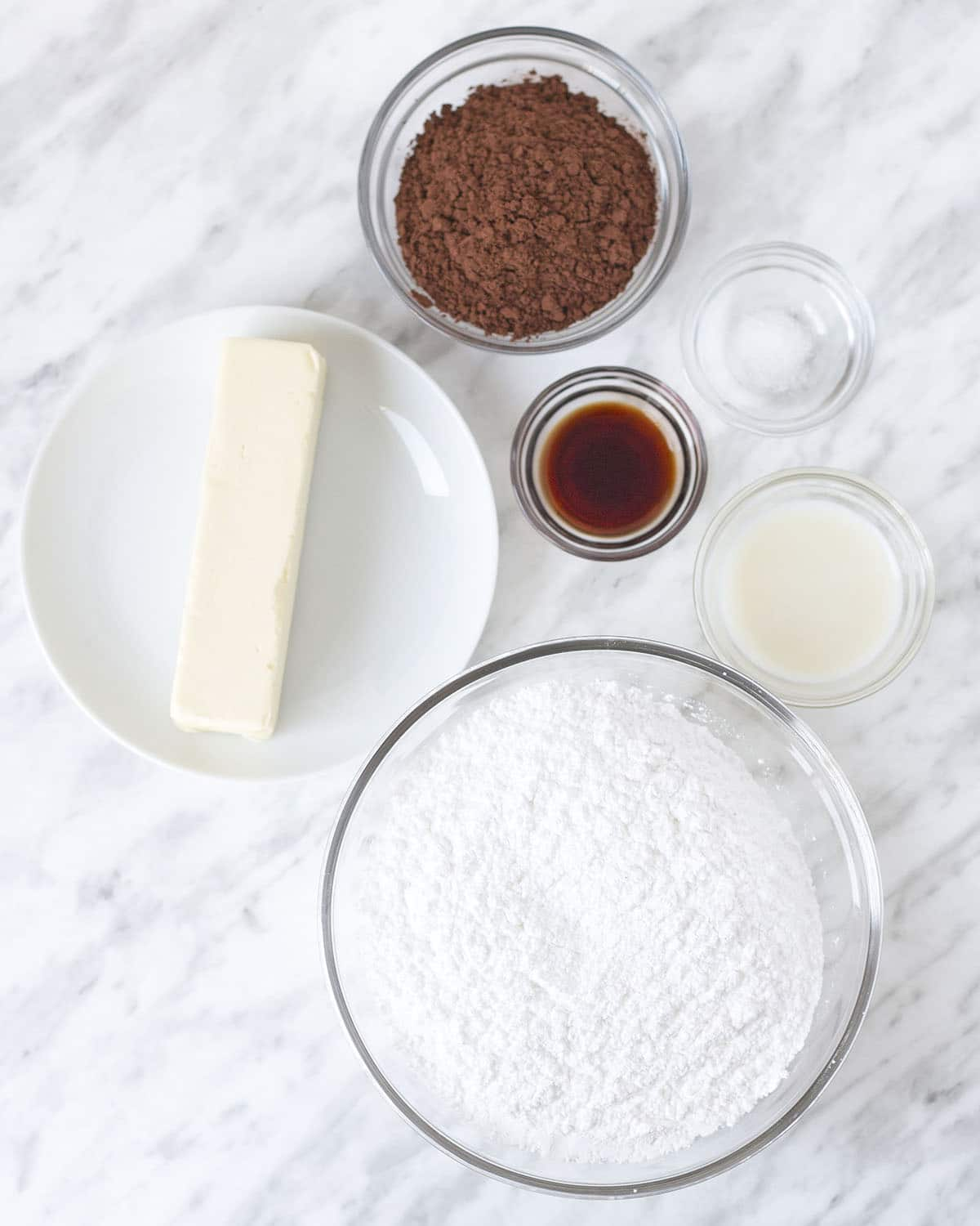 Overhead shot of all the ingredients needed to make vegan chocolate icing, each ingredient is in a separate dish or bowl.
