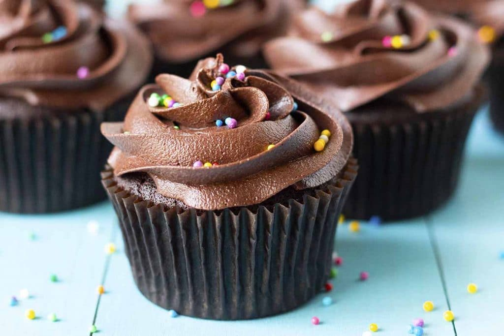A close up picture of a chocolate cupcake sitting on a light blue table.