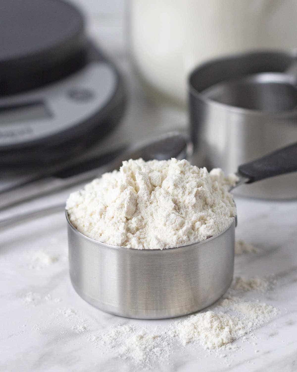 A measuring cup filled with flour, cup is sitting on a marble counter surface.